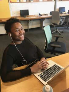 Shayna smiling at the camera while sitting at a desk with a laptop in front of her
