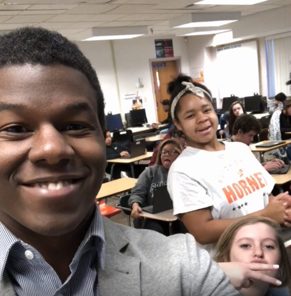 Rashad in his classroom with three students all looking at the camera