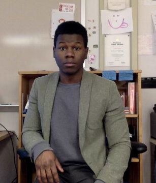 Rashad looking at the camera while sitting in his chair in his classroom